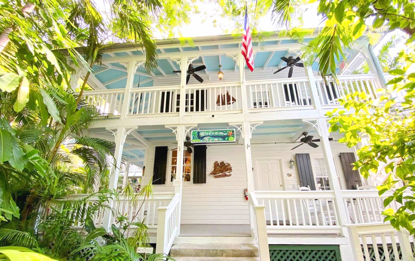 Entrance to a guesthouse in key west porch with sun shining lush tropical foliage